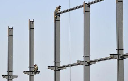 Labourers install steel frames to a new food factory in Taiyuan