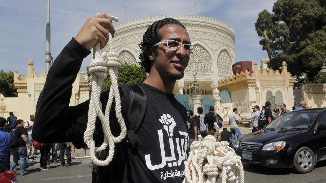 A member of Egypt's April 6 Youth Movement distributes nooses in front of the presidential palace in Cairo, Egypt, Saturday, April 6, 2013. The group is rallying to mark its fifth anniversary and to protest against President Mohammed Morsi. (AP Photo/Amr Nabil)