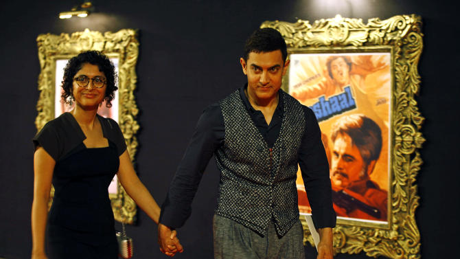 "In this Monday, Nov. 12, 2012 photo, Bollywood star Aamir Khan arrives with his wife Kiran Rao to attend the premiere of the film ""Jab Tak Hai Jaan"" or ""As Long As I Am Alive"" in Mumbai, India. Bollywood stars turned out in strength at the premiere of the movie for a final homage to movie mogul Yash Chopra, who died last month days after finishing the film. Chopra was known as the ""King of Romance"" for creating classic love stories that were immensely popular. (AP Photo/Rafiq Maqbool)"