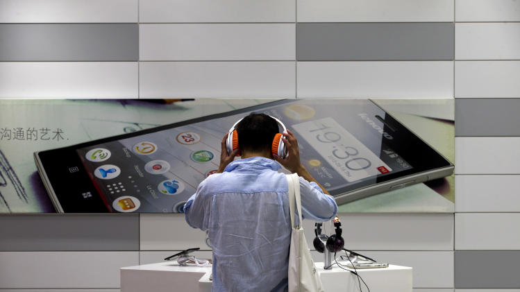 A man tries out a smartphone device on display at a Lenovo flagship experience store in Beijing, China Thursday, Aug. 15, 2013. Lenovo Group says it is evolving quickly into a supplier of wireless computing, driven by booming sales of smartphones and tablets as consumers shift away from desktop computers. (AP Photo/Andy Wong)