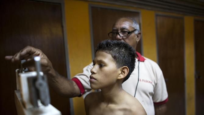 In this May 24, 2012 photo, Miguel Uzcategui, 13, is weighed by his boxing coach known as Polanco, at a boxing gym in Caracas, Venezuela. Every weekend, boys line up with their gloves to slug it out in a boxing ring that moves around Caracas from parks to plazas to streets in the slums. They're participating in a program supported by the Venezuelan government that aims not only to develop standout fighters but also to expand the sport's reach and give poor teenagers an outlet to stay away from crime, alcohol and drugs. Uzcategui says the sport has given him goals as well as improved self-confidence. (AP Photo/Ariana Cubillos)