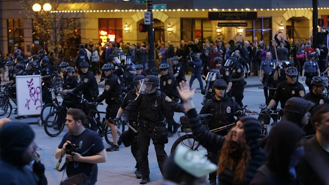 Seattle Police officers try to clear an intersection of protesters during a May Day march that began as an anti-capitalism protest and turned into demonstrators clashing with police, Wednesday, May 1, 2013, in downtown Seattle. (AP Photo/Ted S. Warren)