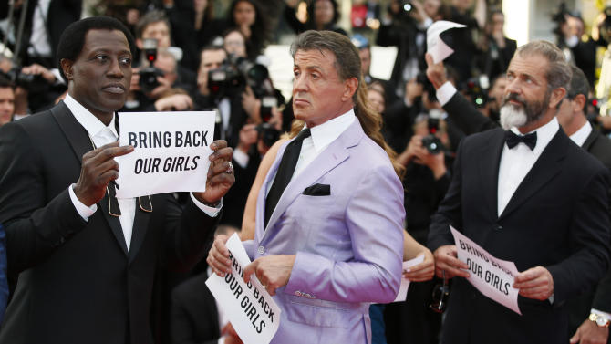 "From left, the cast of The Expendables Wesley Snipes, Sylvester Stallone, and Mel Gibson hold up banners reading, ""Bring back our girls"", part of a campaign calling for the release of nearly 300 abducted Nigerian schoolgirls being held by Nigerian Islamic extremist group Boko Haram, as they arrive for the screening of The Homesman at the 67th international film festival, Cannes, southern France, Sunday, May 18, 2014. (AP Photo/Alastair Grant)"