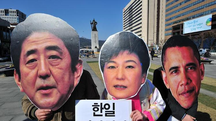 South Korean activists wear the masks of South Korean President Park Geun-Hye (C), Japanese Prime Minister Shinzo Abe (L) and US President Barack Obama (R) during an anti-government protest in Seoul on March 21, 2014