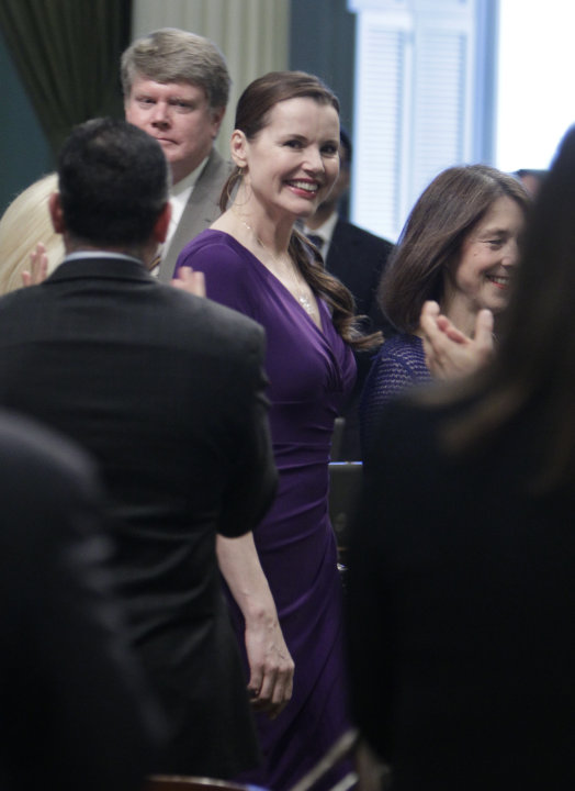 Actress Geena Davis receives a standing ovation from members of the state Assembly as she is escorted down the center aisle by Assemblywoman Nancy Skinner, D-Berkeley, right, at the Capitol in Sacrame