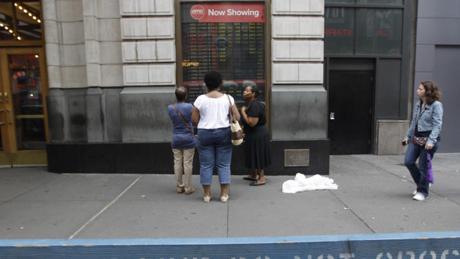 "People read the movie timetable from behind a police barricades set up outside a movie theatre screening ""The Dark Knight Rises,"" Friday, July 20, 2012 in New York.  Some theaters and police around the U.S. stepped up security at daytime showings of the new Batman movie Friday after the massacre in Colorado, and while many fans were undeterred by the tragedy, others were nervous about going to see the film. (AP Photo/Mary Altaffer)"
