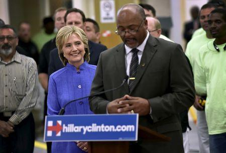 Democratic U.S. presidential candidate Hillary Clinton smiles as she receives an endorsement from the International Union of Painters and Allied Trades President Kenneth Rigmaiden during a visit to an IUPAT training center in Las Vegas
