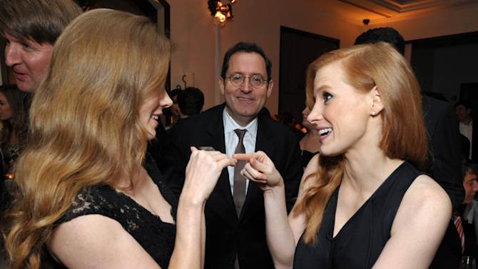 Amy Adams, left, and Jessica Chastain speak at The Hollywood Reporter Nominees' Night at Spago on Monday, Feb. 4, 2013, in Beverly Hills, Calif. Looking on in background is Michael Barker, co-president and co-founder of Sony Pictures Classics. (Photo by John Shearer/Invision for The Hollywood Reporter/AP Images)