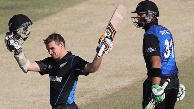 New Zealand batsman Tom Latham (L) raises his bat after reaching his century during the second one-day international against Zimbabwe at Harare Sports Club at Harare on August 4, 2015