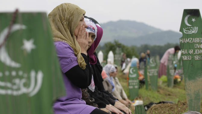 Bosnian Muslim women pray among wooden grave markers during mass funeral in the eastern Bosnian town of Kalesija, 120 kms northeast of Sarajevo, on Saturday, June 2, 2012. Thousands have gathered in the eastern Bosnian town of Kalesija to bury the remains of 32 Muslim Bosniaks killed at the start of the country's 1992-95 war. The victims' remains were discovered in numerous mass graves and they were identified through DNA analysis. (AP Photo/Amel Emric)