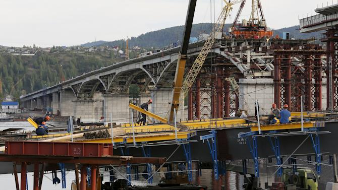 Workers are seen at construction site at highway bridge across Yenisei River in Krasnoyarsk