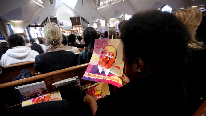 Volunteers roll up posters marking the 50th anniversary of Dr. Martin Luther King Jr.'s 'I Have a Dream' speech during the annual holiday commemorative service in his honor at the Ebenezer Baptist Church, Monday, Jan. 21, 2013, in Atlanta. The nation will honor civil rights leader Martin Luther King Jr. on Monday, the same day as it celebrates the inauguration of the first black president to his second term. (AP Photo/David Goldman)