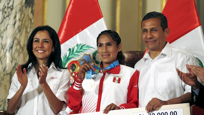 Peru's President Ollanta Humala presents a cheque to Gladys Tejeda, gold medalist in the women's marathon at the 2015 Pan American Games in Toronto, during a ceremony in Lima