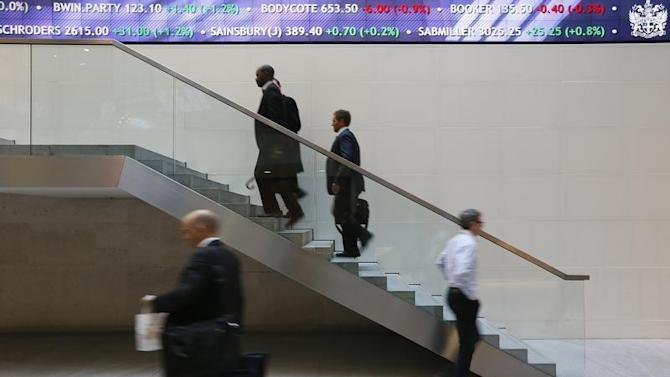 People walk past an electronic information board at the London Stock Exchange in the City of London