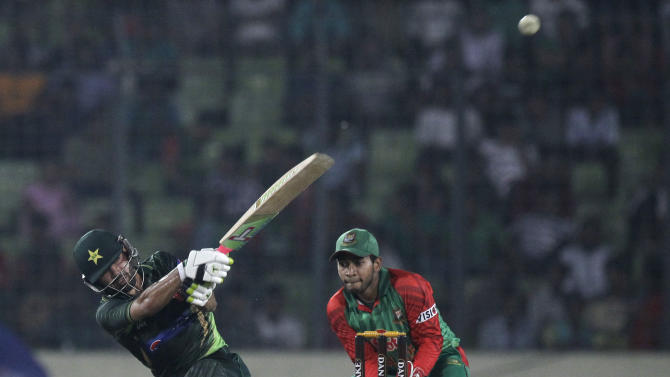 Pakistan's Mohammad Rizwan, left, plays a shot, as Bangladesh's wicketkeeper Mushfiqur Rahim watches during their first one-day international cricket match in Dhaka, Bangladesh, Friday, April 17, 2015. (AP Photo/ A.M. Ahad)