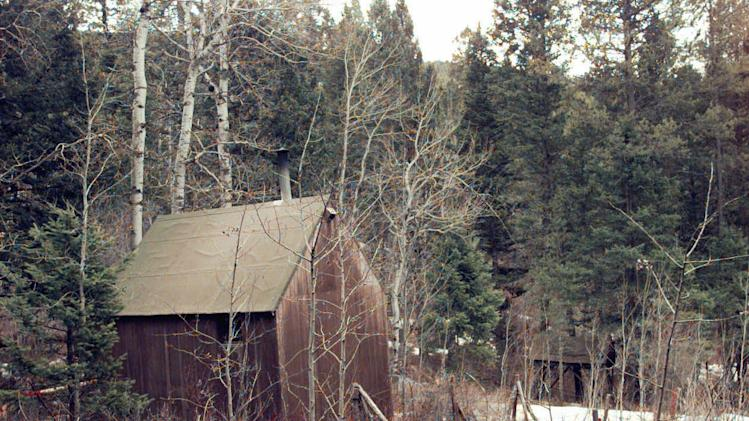 "FILE - In this April 6, 1996 file photo, the cabin of Unabomber Theodore Kaczynski, partially surrounded by white, plastic tape, sits at the end of a muddy, private road, hidden in a wooded setting about 300 yards from the nearest neighbor in Lincoln, Mont. The 1.4-acre parcel of land in western Montana that was once owned by Kaczynski is on the market for $69,500. The listing offers potential buyers a chance to own a piece of ""infamous U.S. history"" and says the forested land ""is obviously very secluded. (AP Photo/Elaine Thompson, File)"