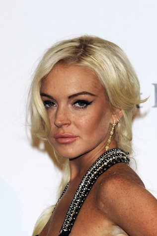 FILE - Lindsay Lohan poses at the Amfar charity event, part of the Fashion Week in Milan, Italy, in this Sept. 23, 2011 file photo. Lohan returns to a Los Angeles court on Wednesday Nov. 2, 2011 for a probation violation hearing that could end with the starlet returning for jail (AP Photo/Giuseppe Aresu, File)
