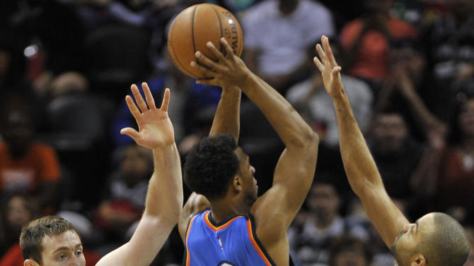 Oklahoma City Thunder guard Ish Smith, center, shoots against San Antonio Spurs guard Tony Parker, right, of France, and Spurs forward Aron Baynes, of Australia, during the first half an NBA basketball game, Thursday, Dec. 25, 2014, in San Antonio. (AP Photo/Darren Abate)