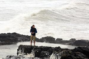A man stands on a rocky outcrop as waves roll in to …