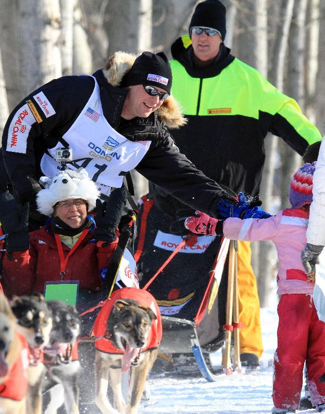 Ed Stielstra greets fans as he drives his team during the ceremonial start of the Iditarod Trail Sled Dog Race Saturday, March 2, 2013, in Anchorage, Alaska. The competitive portion of the 1,000-mile race is scheduled to begin Sunday in Willow, Alaska. (AP Photo/Dan Joling)