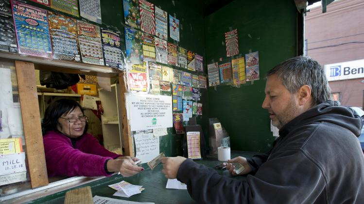 Norn Phneo sells Powerball tickets to Billy Fulginiti, of Philadelphia for himself and his coworkers, Wednesday, Nov. 28, 2012, in Philadelphia. (AP Photo/Matt Rourke)