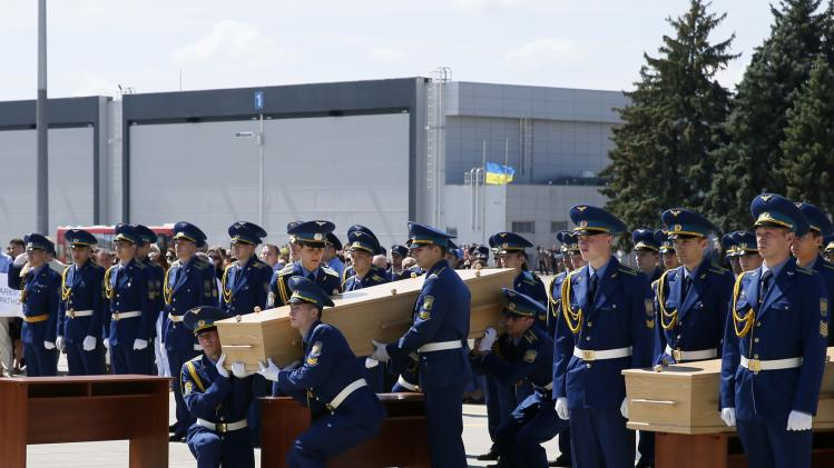 Honour guards carry a coffin of a Malaysia Airlines MH17 victim at Kharkiv airport