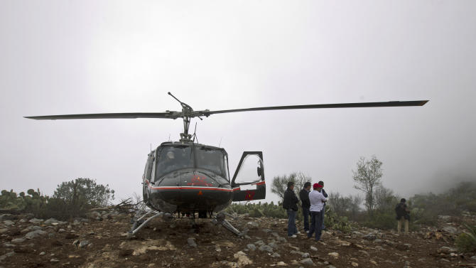 A rescue helicopter with members of the Mexican General Civil Aeronautic Directorate (DGAC) stand on top of the hill right next to the canyon where U.S.-born singer Jenni Rivera's jet crashed near the town of Iturbude, Mexico, Dec. 10, 2012. Rivera's life was cut short at its peak on Sunday by an airplane crash in northern Mexico that also killed six friends and co-workers. (AP Photo/Hans Maximo Musielik)