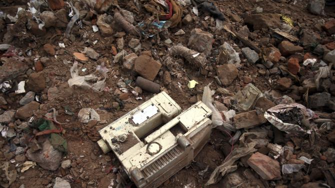 A sewing machine lies in the rubble from the collapsed garment factory building, Saturday, May 4, 2013 in Savar, near Dhaka, Bangladesh. In the aftermath of last week's building collapse that killed more than 530 people, Bangladesh's garment manufacturers may face a choice of reform or perish. Home to five factories that supplied clothing to retailers in Europe and the United States, the shoddily constructed building's collapse has put a focus on the high human price paid when Bangladeshi government ineptitude, Western consumer apathy and global retailing's drive for the lowest cost of production intersect. (AP Photo/Wong Maye-E)