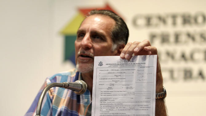 "Cuban agent Rene Gonzalez, 56, holds up his U.S. certificate of loss of nationality during a press conference in Havana, Cuba, Friday, May 10, 2013. Gonzalez who spent 13 years in a U.S. prison renounced his American citizenship Monday, May 6, 2013, as part of a deal that allows him to avoid returning to the United States to serve out the remainder of his probation. Gonzalez is one of the so-called ""Cuban Five"" intelligence agents convicted in 2001 of spying on U.S. military installations in South Florida, exile groups and politicians. (AP Photo/Franklin Reyes)"