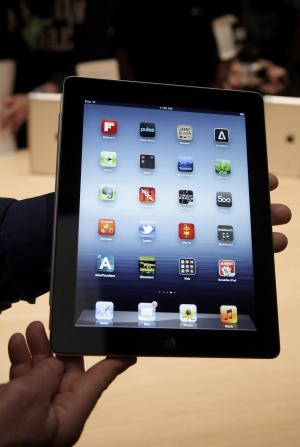"FILE - In this March 7, 2012 file photo, an Associated Press reporter holds up the new iPad during an event in San Francisco. Rumors of a smaller iPad, or ""iPad mini"" have percolated ever since the first iPad was launched two years ago. This time around, they're fed by media reports from South Korea, China and Taiwan, saying Apple has ordered Samsung screens that are 7.86 inches measured on the diagonal. That would make for a screen about half the size of the current iPad, which has a diagonal measurement of 9.7 inches.  (AP Photo/Jeff Chiu, File)"