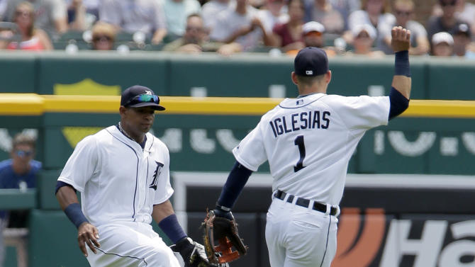A double hit by Toronto Blue Jays' Jose Reyes lands between Detroit Tigers left fielder Yoenis Cespedes and shortstop Jose Iglesias during the first inning of a baseball game Sunday, July 5, 2015, in Detroit. (AP Photo/Duane Burleson)