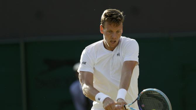 Tomas Berdych of the Czech Republic hits a shot during his match against Gilles Simon of France at the Wimbledon Tennis Championships in London