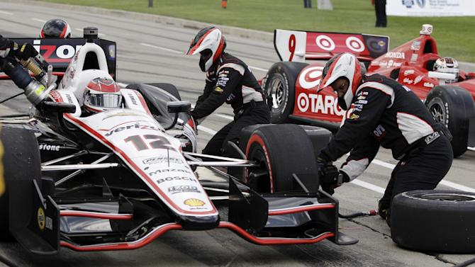 Will Power, left, of Australia, makes a pit stop as Scott Dixon, right, of New Zealand, passes during IndyCar's Detroit Grand Prix auto race on Belle Isle in Detroit, Sunday, June 3, 2012. (AP Photo/Carlos Osorio)