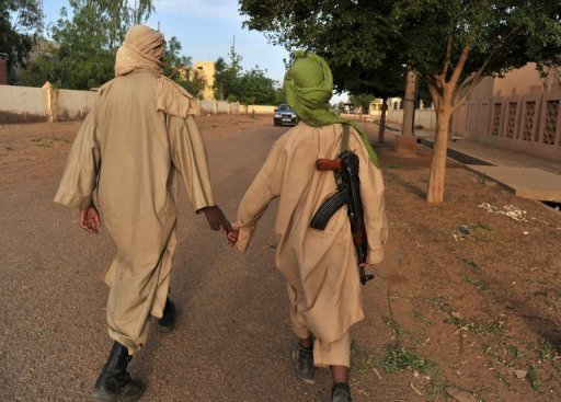 Two young fighters of the Islamist group Movement for Oneness and Jihad in West Africa (MUJAO) in Gao, Mali on July 17, 2012. Armed groups occupying Timbuktu in northern Mali used pickaxes on Sunday to smash up any remaining mausoleums in the ancient city, an Islamist leader said.