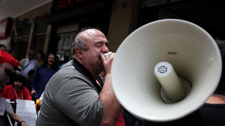 A blind demonstrator shouts slogans  through a megaphone outside the interior ministry during a protest demanding welfare payments, in Athens, Thursday, May 24, 2012. People with disabilities have not received government  welfare payments for two months. Greece has been caught in an acute financial crisis for two and a half years, and has only avoided bankruptcy through international rescue loans. (AP Photo/Petros Giannakouris)