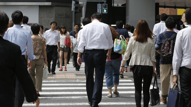 People walk on a pedestrian crossing in Tokyo, Tuesday, July 30, 2013. Japan's industrial output fell in June for the first time in five months, the government said Tuesday as it released data highlighting the fragility of the recovery in the world's No. 3 economy. (AP Photo/Shizuo Kambayashi)