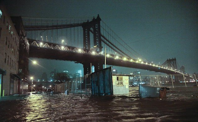 Streets are flooded under the Manhattan Bridge in the Dumbo section of Brooklyn, N.Y., Monday, Oct. 29, 2012. Sandy continued on its path Monday, as the storm forced the shutdown of mass transit, scho