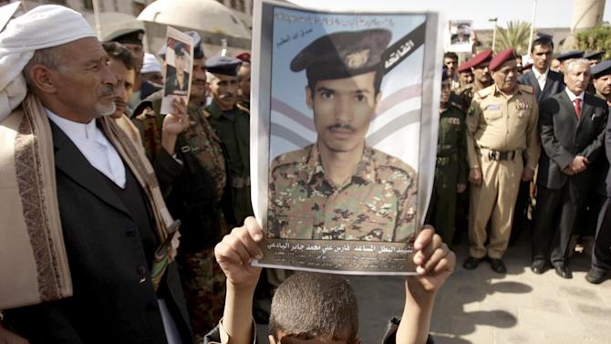 """FILE -- In this Monday, Aug. 20, 2012 file photo a Yemeni boy holds a poster depicting his father, who was killed in an attack in the city of Aden by suspected al-Qaida militants, during his funeral in Sanaa, Yemen. Al-Qaida committed """"horrific"""" rights abuses during its 16 months in power between February 2011 and June 2012 in southern Yemen, the London-based rights group Amnesty International charged in a report released Tuesday. The report also accuses Yemen's government of abuses. (AP Photo/Hani Mohammed, File)"""