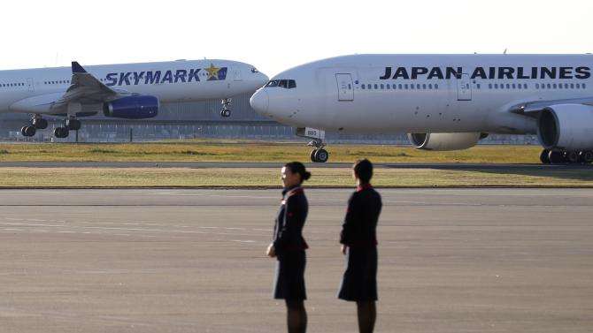 Flight attendants of JAL stand in front of the company's aircraft as a Skymark Airlines aircraft lands at Haneda airport in Tokyo