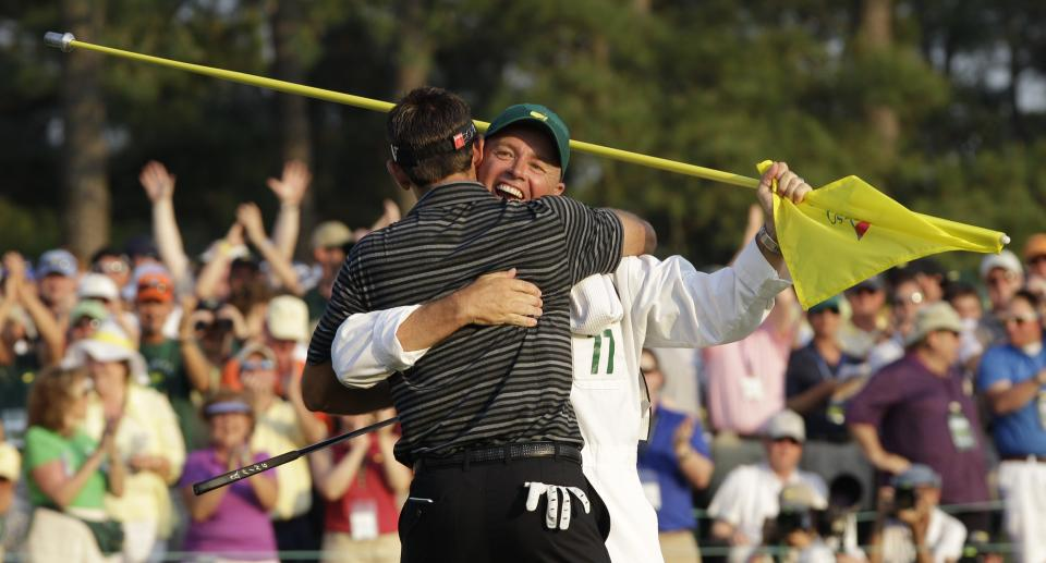Charl Schwartzel of South Africa hugs his caddie Greg Hearmon after his birdie putt on the 18th hole during the final round of the Masters golf tournament Sunday, April 10, 2011, in Augusta, Ga. (AP Photo/Chris O'Meara)