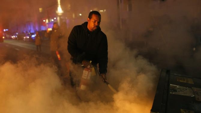 A local resident attempts to extinguish a street fire set by protesters during a demonstration in Oakland
