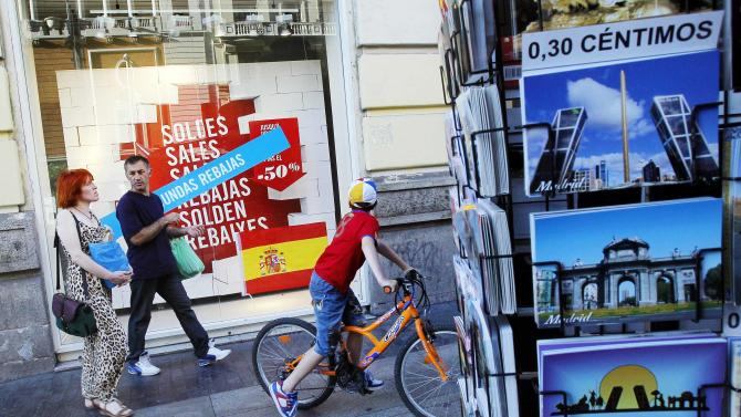 A couple and a child wearing a Spanish soccer jersey pass by a shop with a discount sale sign and samples of postcards including one with Bankia bank buildings' picture, top, on the day of the Euro 2012 soccer final match in Madrid, Spain, Sunday, July 1, 2012. Bankia is one of several big banks that will need billions in rescue loans. (AP Photo/Andres Kudacki)