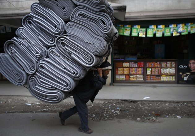 A Nepalese porter carrying a pile of mats walks along the streets of Kathmandu