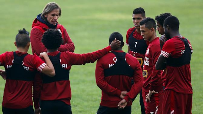 Peru's soccer team head coach Gareca talks with his players during a training session in preparation for the Copa America third place match in Santiago, Chile