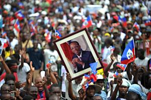 Haitian supporters of Maryce Narcisse wave flags and …