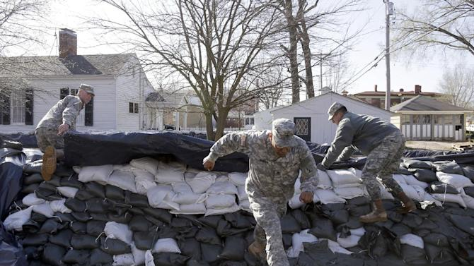 Members of the Missouri National Guard work to shore up a temporary levee in an effort to hold back the swollen Mississippi River Saturday, April 20, 2013, in Clarksville, Mo. Communities along the Mississippi River and other rain-engorged waterways are waging feverish bids to hold back floodwaters that may soon approach record levels. (AP Photo/Jeff Roberson)