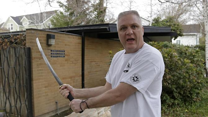 Kent Hendrix, 47, draws his sword near his house Tuesday, April 23, 2013, in Salt Lake City. Hendrix, a Samurai sword-wielding Mormon bishop came to the aid of a woman who was being attacked in front of his house. Hendrix woke up Tuesday to his teenage son pounding on his bedroom door and telling him somebody was being mugged. Hendrix grabbed a 29-inch Samurai sword and rushed out the door. He says the man attacking a woman jumped back and ran down the street after he drew the sword. The man was chased until he jumped in his car and drove away. (AP Photo/Rick Bowmer)
