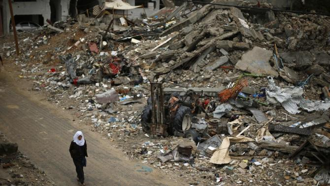A Palestinian school girl walks past the ruins of houses that witnesses said were destroyed by Israeli shelling during the most recent conflict between Israel and Hamas, on a rainy day in Beit Hanoun