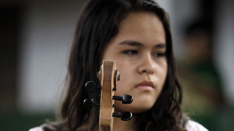 "In this Dec. 11, 2012 photo, musician Maria Rios, 16, holds her violin made of recycled materials before practicing with ""The Orchestra of Instruments Recycled From Cateura""  in Cateura, a vast landfill outside Paraguay's capital of Asuncion, Paraguay.  ""My mother signed me up in teacher Chavez's school three years ago. I was really bothered that she hadn't asked me first, but today I'm thankful because she put my name in as someone who wanted to learn violin,"" Maria said. (AP Photo/Jorge Saenz)"