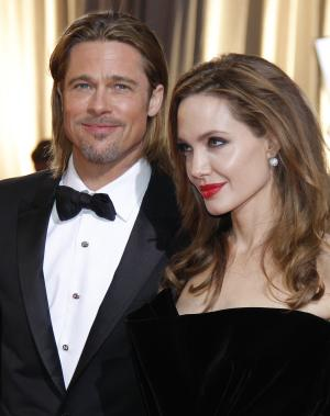 """FILE - This Feb. 26, 2012 file photo shows actors Brad Pitt, left, and Angelina Jolie at the 84th Academy Awards in the Hollywood section of Los Angeles. Pitt says it was important for his partner, Angelina Jolie, to share her story about having her breasts removed to avoid cancer """"and that others would understand it doesn't have to be a scary thing."""" In an interview in USA Today on wednesday, May 15, 2013, the actor said: """"In fact, it can be an empowering thing, and something that makes you stronger and makes us stronger.""""  (AP Photo/Amy Sancetta, file)"""